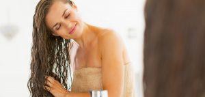 mujer peinando su cabello húmedo frente al espejo