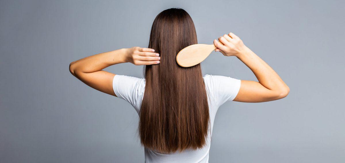 Mujer peinándose su cabello largo de espaldas